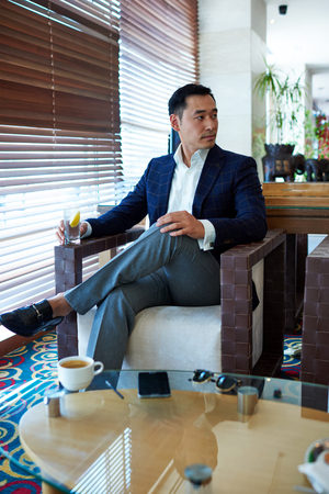Portrait of a successful managing director enjoying a drink while waiting for a business partners in cozy restaurant, handsome men entrepreneur with serious face looking aside while relaxing in cafe Imagens