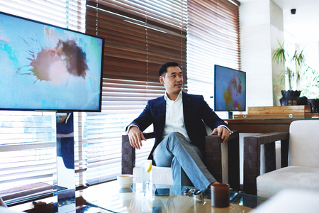 publicly: Portrait of confident businessman sitting in cafe near publicly tv screen with copy space for your advertising content, successful asian men entrepreneur relaxing in restaurant during work break Stock Photo