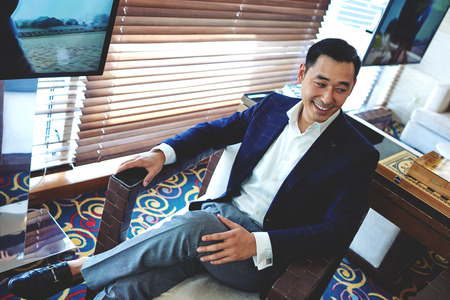 Cheerful smiling businessman sitting in modern restaurant resting after hard work day, happy asian men dressed in elegant suit enjoying free time, intelligent male entrepreneur relaxing in cafe Stock Photo