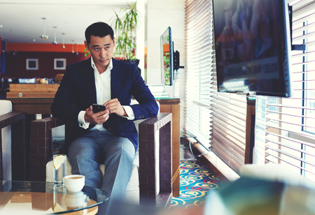 wealthy lifestyle: Portrait of a young handsome man watching the news on television during work on his mobile phone, successful managing director using cell telephone during coffee break in modern cafe inside Stock Photo