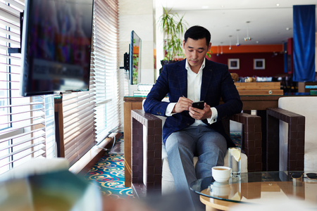 Young Chinese  businessman dressed in luxury suit chatting on his cell telephone while sitting in modern coffee shop inside, office worker typing text message on mobile phone while relaxing in cafe Stock Photo