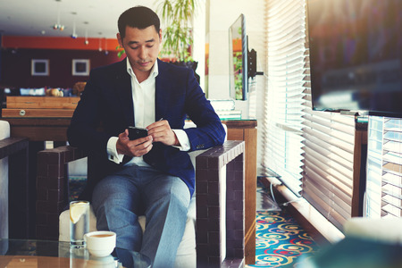 modern lifestyle: Portrait of young confident men entrepreneur dressed in luxury suit chatting on cell telephone during work break, intelligent male using his mobile phone while preparing for business meeting in office Stock Photo