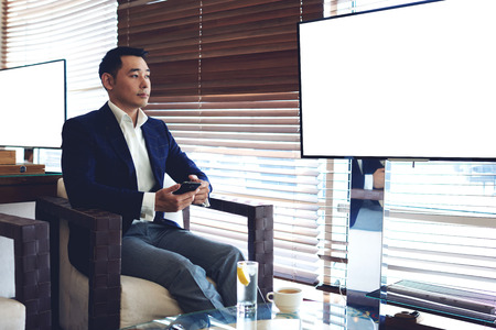 businessman waiting call: Young managing director using smart phone while sitting in modern office near publicly blank tv screen with copy space,successful businessman waiting for a call on his cell telephone during breakfast