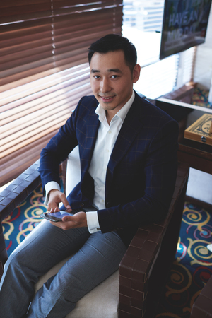 Portrait of young asian successful managing director holding cell telephone while sitting in office space, elegant men dressed in luxury suit using his smart phone during lunch break in cafe inside