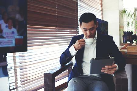 Portré, fiatal, elegáns férfi olvasó e-könyv a digitális tábla, miközben iszik ital kávézó belsejében, magabiztos üzletember segítségével touch pad távoli munka, miközben nyugalomban kávészünet