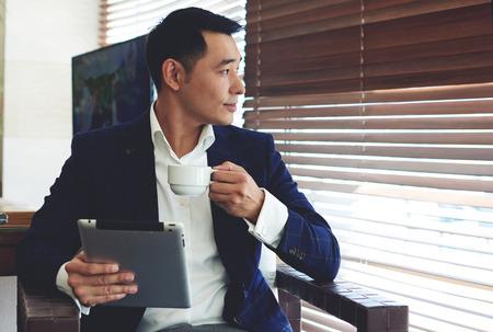 Portré, fiatal, magabiztos üzletember élvezi kávét, miközben a munka az ő digitális tabletta iroda belső, átgondolt ázsiai férfi elegáns öltöny gazdaság touch pad pihenve modern kávézó