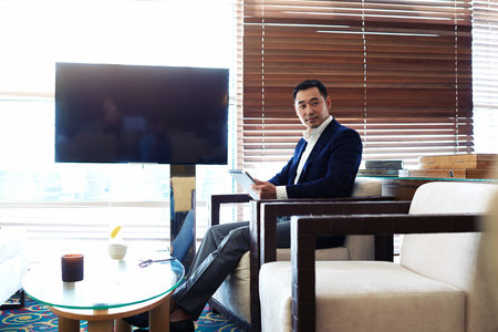 Portrait of a young managing director with serious face working on touch pad during work break, businessman holding digital tablet while sitting in restaurant near empty blank screen with copy space