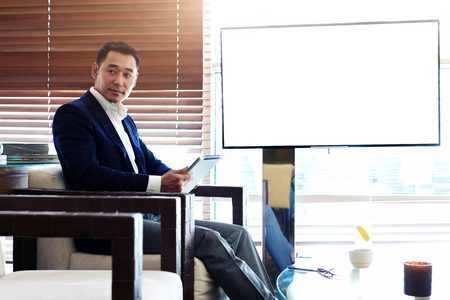 Successful man in elegant suit using digital tablet during preparation for the business meeting, confident asian male working on touch pad while sitting in cafe near empty blank screen with copy space Stock Photo