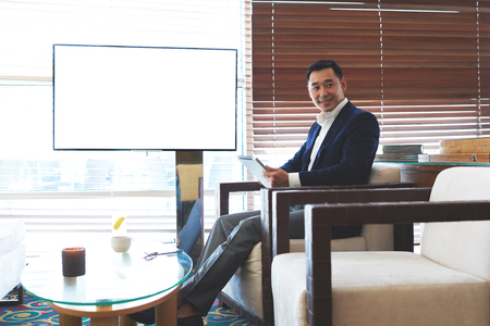 wealthy lifestyle: Smiling asian male entrepreneur working on touch pad while sitting in modern coffee shop near empty blank screen with copy space, successful man in elegant suit reading e-book on his digital tablet