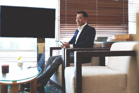 귀하의 콘텐츠에 대 한 복사 공간이있는 빈 화면 근처 사무실에 앉아있는 동안 디지털 태블릿을 들고 웃는 성공적인 아시아 사업가의 초상화 터치 패