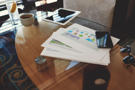 capital gains: Digital tablet and mobile phone with blank copy space screen for your advertising content or text message, paper documents with charts on a glass table in modern coffee shop