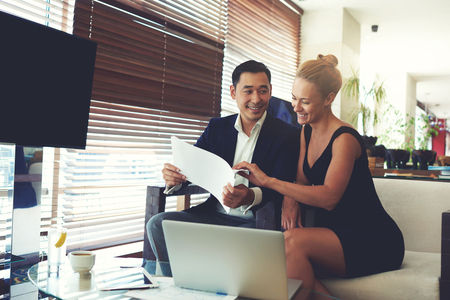 wealthy lifestyle: Portrait of a smiling cheerful business men and women watching together working papers while sitting with laptop computer in office space, young happy leadership received good results in their job Stock Photo