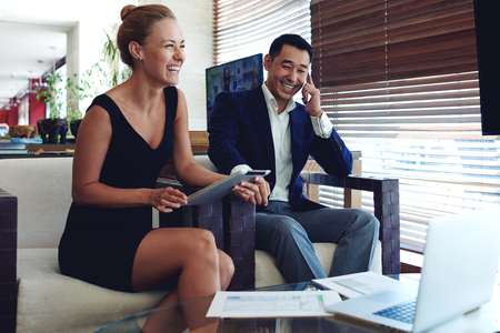 employers: Portrait of two smiling cheerful entrepreneurs preparing for meeting, young woman using touch pad, intelligent men having mobile phone conversation, smart employers busy working in modern office space