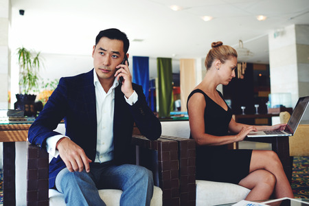 serious face: Handsome businessman with serious face discussing work issues by mobile phone, young smart woman working on laptop computer, successful male and female entrepreneurs sitting in modern office interior