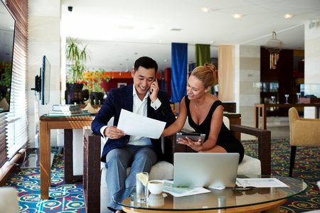 Successful smiling woman entrepreneur reveals documents his men colleague while work on digital tablet, cheerful intelligent business man look at working papers while having mobile phone conversation