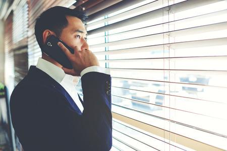 Fél hosszúság portré, fiatal, ázsiai, intelligens férfi beszél telefonon, miközben keresi irodai ablakban, benne szakdolgozói rendelkező mobiltelefon beszélgetés üzlettársa