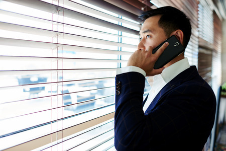 Portrait of young confident successful businessman dressed in elegant suit having mobile phone conversation, smart asian men entrepreneur talk on his cellphone while standing in office space interior Stock Photo