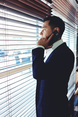 Portrait of a young successful intelligent men entrepreneur having telephone conversation while standing near office window, businessman dressed in luxury elegant clothes talking on his mobile phone