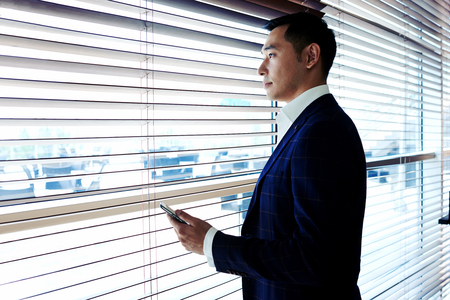 Young confident boss holding his mobile phone while standing near office window with venetian blinds, successful man entrepreneur with serious face using cell telephone with copy space area for text