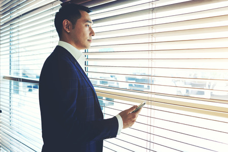 businessman waiting call: Portrait of a confident young businessman holding cell telephone while standing near office window, intelligent men in elegant suit waiting for a call on his mobile phone while resting after meeting