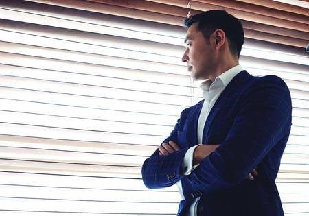 Fele hossza portré egy fiatal férfi súlyos vállalkozó öltözött luxus ruha keresztbe fegyver áll közel irodája ablakán, ügyvezető gondolt valamit, mielőtt üzleti találkozó
