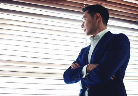 Half length portrait of a young serious men entrepreneur dressed in luxury clothes with crossed arms standing near office window, managing director thinking about something before business meeting