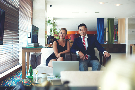 rich life: Portrait of a young two professional workers relaxing after business meeting while sitting with net-book in office, woman and men entrepreneurs dressed in elegant clothes resting after conference