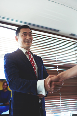 Portrait of a smiling young asian men entrepreneur shaking hands with his work colleagues, successful managing director businessman handshake with someone in honor of conclusion of the contract