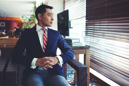 大きな窓の近くのモダンなオフィスのインテリア、会議の前に何かについて考えるをエレガントなスーツのインテリジェントな男性起業家に座って