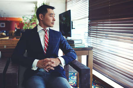 blinds: Portrait of young confident asian businessman with serious face sitting in modern office interior near big window, intelligent men entrepreneur in elegant suit thinking about something before meeting Stock Photo