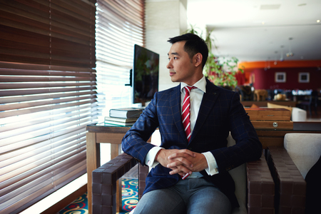 businessman thinking: Portrait of a young successful asian businessman thinking about something while sitting in modern office interior space, thoughtful men entrepreneur resting after conference or meeting with partners Stock Photo