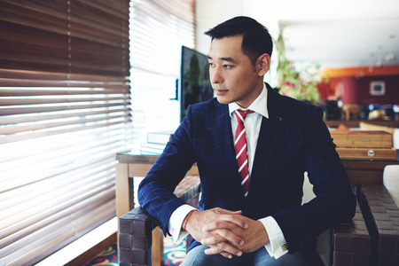 Portrait of a asian men entrepreneur dressed in luxury suit waiting for the colleagues while sitting in office space interior, young managing director in formal wear relaxing after business meeting