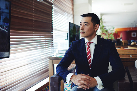 Portrait of asian businessman watching television while sitting in modern private room of the office, confident young professional dressed in elegant clothes relaxing in the armchair in interior