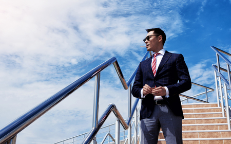 business lifestyle: Portrait of young successful director standing with a cigarette against blue sky with copy space,confident asian businessman dressed in formal wear enjoying rest and smoke cigarette outside the office