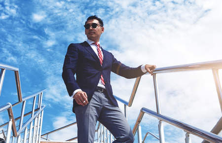 Nézd meg alulról egy fiatal sikeres ügyvezetője állt a cigarettát a szabadban, kék, felhős ég, magabiztos üzletember öltözött luxus ruha pihentető után találkozó vagy konferencia