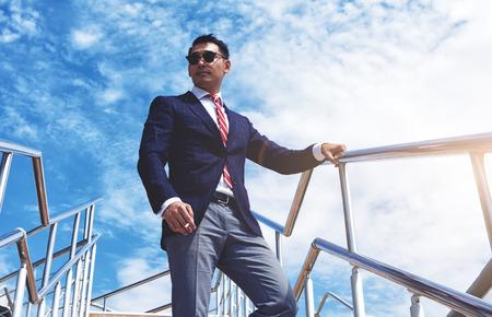 Vue de dessous d'un jeune directeur général de succès debout avec une cigarette à l'extérieur contre le ciel bleu nuageux, homme d'affaires confiants habillé en costume de luxe se détendre après une réunion ou conférence