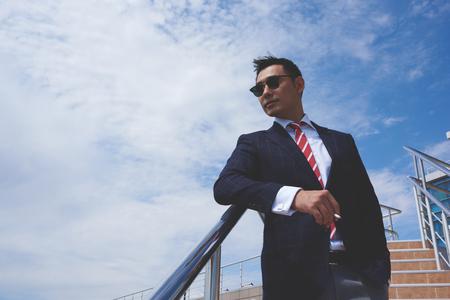 Asiatischer Geschäftsmann in eleganten Anzug stehend gekleidet im Freien vor blauem Himmel mit Kopie Platz für Ihre Werbeinhalte, junge Männer Unternehmer eine Zigarette an der frischen Luft während der Arbeit Pause rauchen