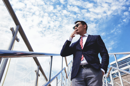 hard day at the office: View from below of young confident businessmen smoking cigarette while standing outside office, successful managing director dressed in stylish clothes relaxing outdoors after hard work day