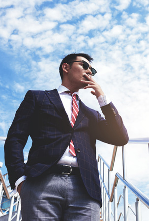 rich life: Portreit of asian men entrepreneur dressed in elegant clothes smoking a cigarette in the fresh air while standing near office building, young professional business men rest outdoors during work break Stock Photo