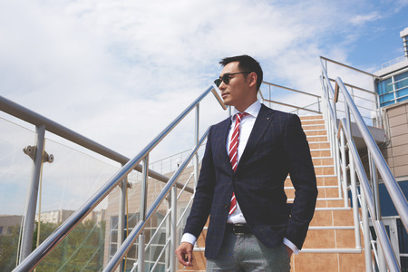 man looking at sky: Portrait of a successful smart asian men dressed in elegant clothes standing on the street while having cigarette during work break, young confident businessman in formal wear resting after hard day Stock Photo