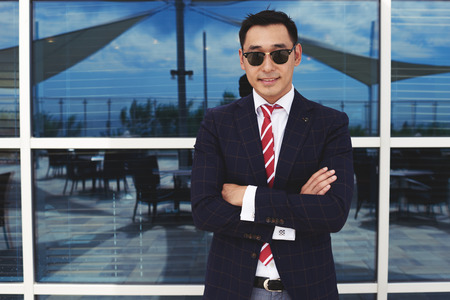 Half length portrait of smiling asian businessman dressed in trendy clothes standing with crossed arms outdoors, happy successful men entrepreneur in formal wear posing against office building