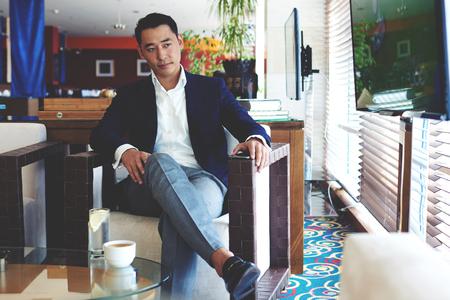 viso uomo: Ritratto di un giovane amministratore delegato di successo guardare le notizie in TV in attesa di partner commerciali in ristorante moderno, sicuro di sé uomini d'affari intelligenti rilassante nel caffè durante la pausa Luch