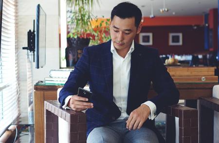 Portré jóképű férfi öltözött luxus ruha beszélgetni az ő okos telefon ülve kényelmes kávézó belsejében, magabiztos ember vállalkozó segítségével mobiltelefonjára pihenve kávézó