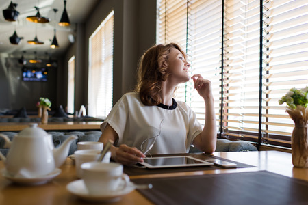 just arrived: Portrait of gorgeous female looking out the window for her friends just arrived to the coffee shop where they meet, young attractive woman sitting with digital tablet and headphones in modern cafe