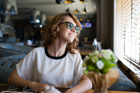 prettiness: Portrait of young gorgeous female smiling to the window while she see her just arrived boyfriend to the coffee shop where they date or meet, attractive woman enjoying the good mood and her recreation