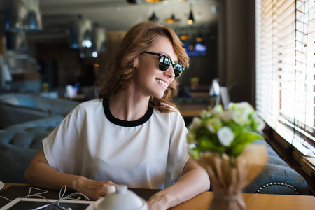 just arrived: Portrait of young gorgeous female smiling to the window while she see her just arrived friends on date or meet, attractive woman enjoying the good mood and her recreation time in modern coffee shop