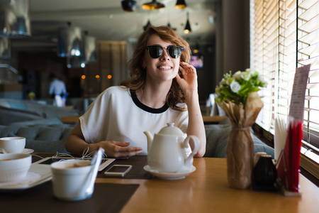charmingly: Portrait of young attractive female sitting in a restaurant enjoying breakfast and her leisure time at weekend, gorgeous female smiling charmingly while spending her recreation in the restaurant