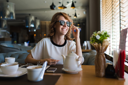 Portrait of attractive young woman smiling charmingly while looking out the window for her friends just arrived to the coffee shop where they meet,gorgeous female enjoying recreation time at breakfast