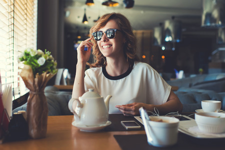 charmingly: Portrait of attractive young woman smiling charmingly while looking out the window for her friends just arrived to the coffee shop where they meet,gorgeous female enjoying recreation time at breakfast