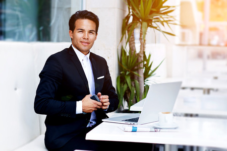 Successful freelancer man work remotely on his laptop computer while sitting at modern restaurant, confident businessman sitting at the table with open net-book and holding mobile phone in the hand